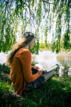 Teenager with book sitting under weeping willow