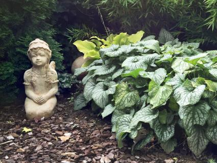 Statue By Plants In Garden