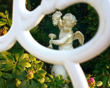 Angel Statue Amidst Plants In Garden