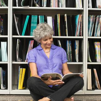 Woman reading magazine in library