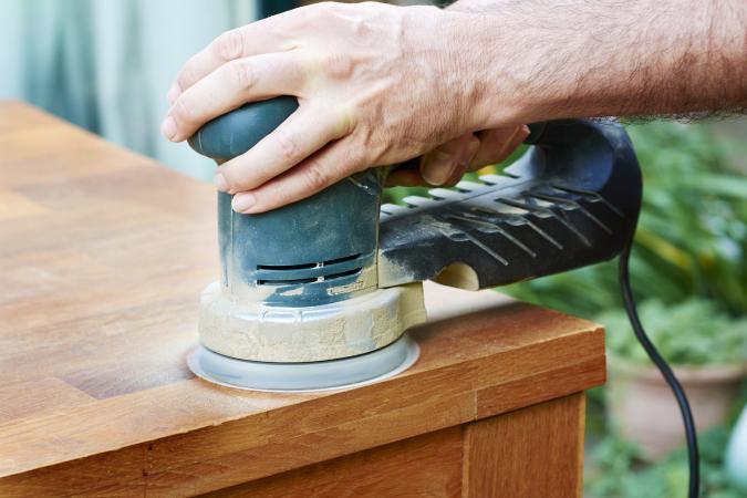 Man sanding an oak table with a random orbital sander