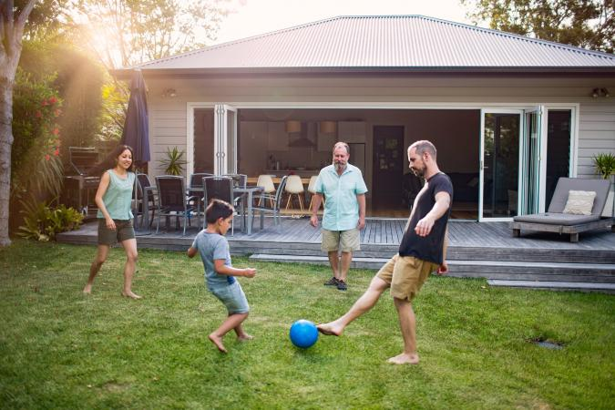 Multi-generation family playing soccer in yard