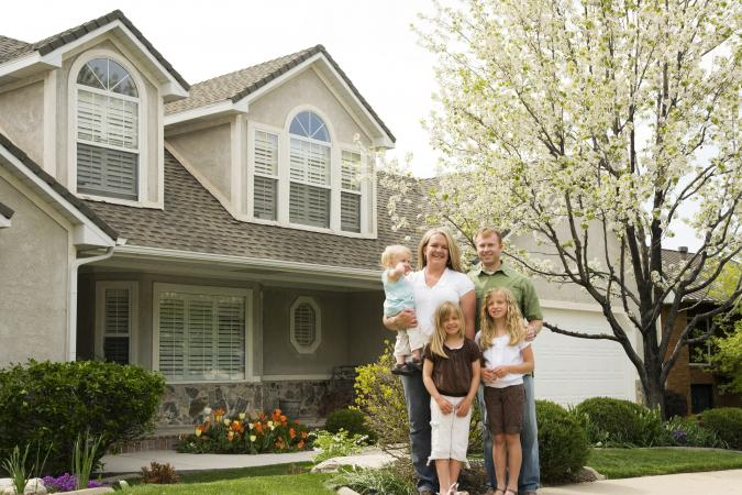 Family of five at home in front of white flower tree