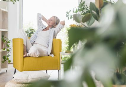 Smiling woman relaxing in armchair at home