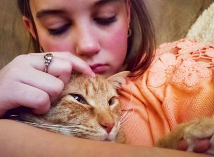 Chica triste acariciando su gato