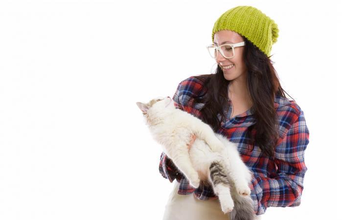 Mujer sonriendo mientras sostiene un lindo gato
