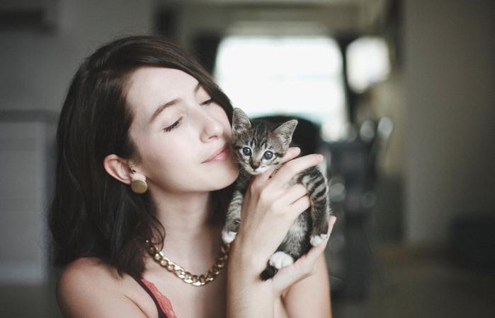 Mujer con un lindo gatito en la mano