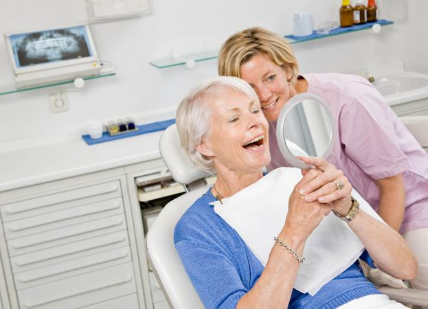 Dental patient looking at dentures