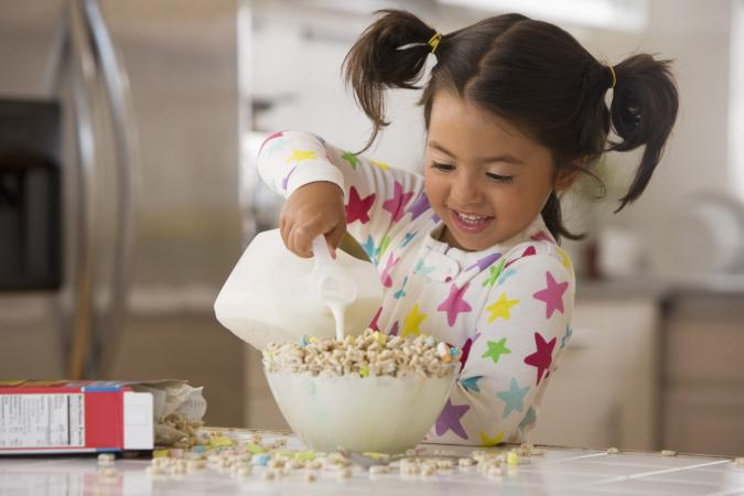 Little girl making bowl of cereal