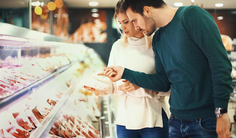 Couple buying fresh meat in supermarket