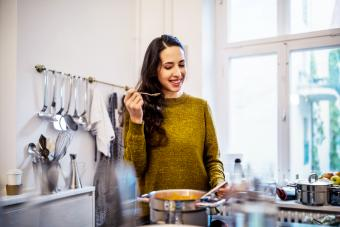Woman tasting soup in kitchen