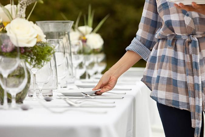 Woman preparing dinner party table
