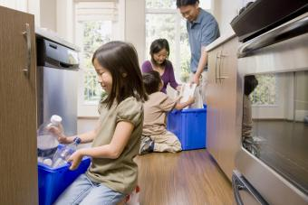 Parents with children recycling in kitchen
