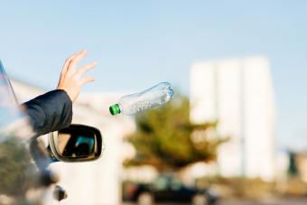 Woman throwing bottle out of car window