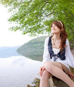 Young woman sitting by lake