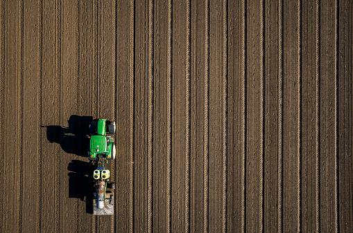 Aerial view tractor driving over dirt