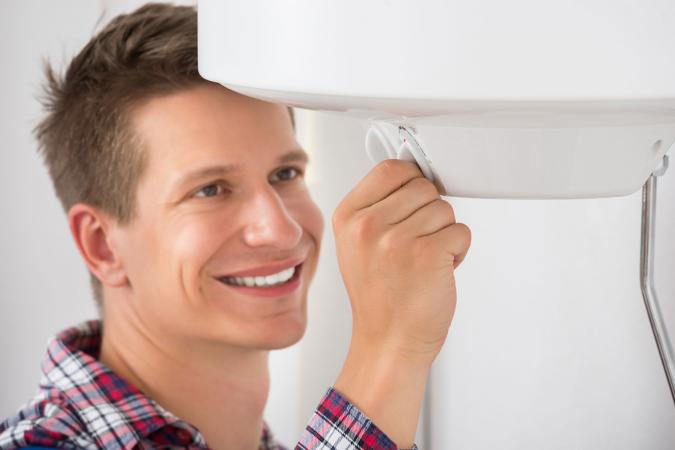 Man adjusting temperature of boiler