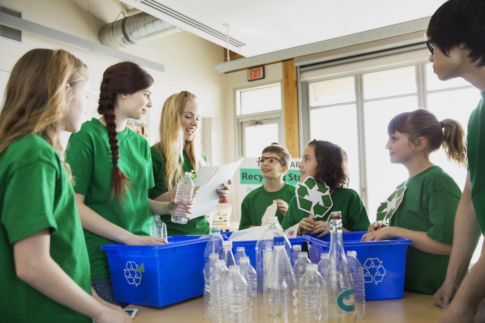 Mentor teaching students to recycle in classroom