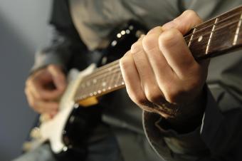Image of man picking a guitar