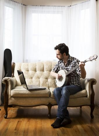 man with banjo and laptop