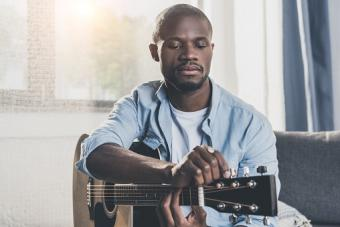 man tuning acoustic guitar