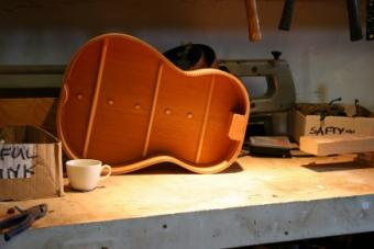 Inside of a classical guitar sitting on a work bench.