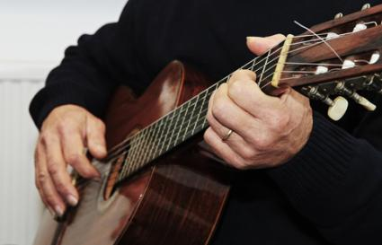 Man strumming a guitar chord