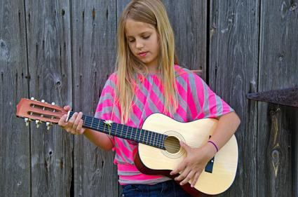 Girl strumming a child's guitar