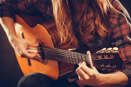 girl writing a song on guitar
