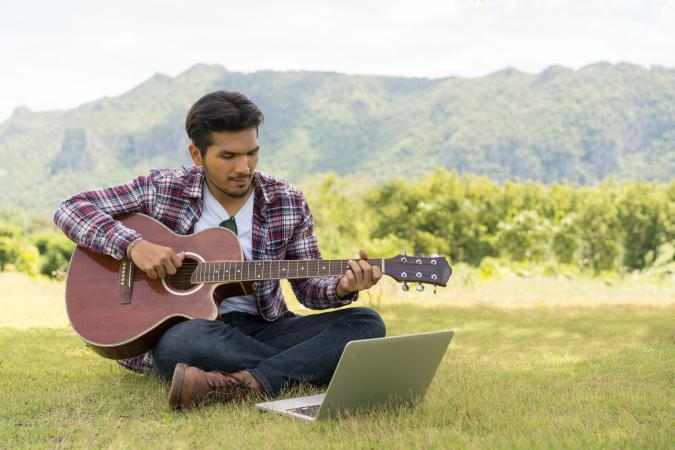 playing guitar while looking at laptop