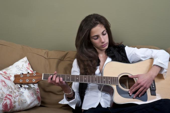 Teenage girl playing the guitar