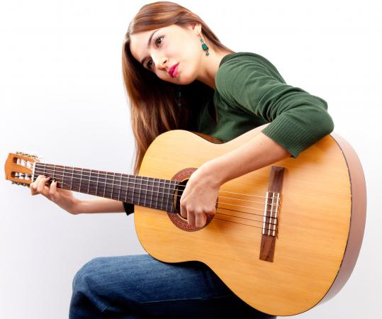 Left-handed woman playing acoustic guitar