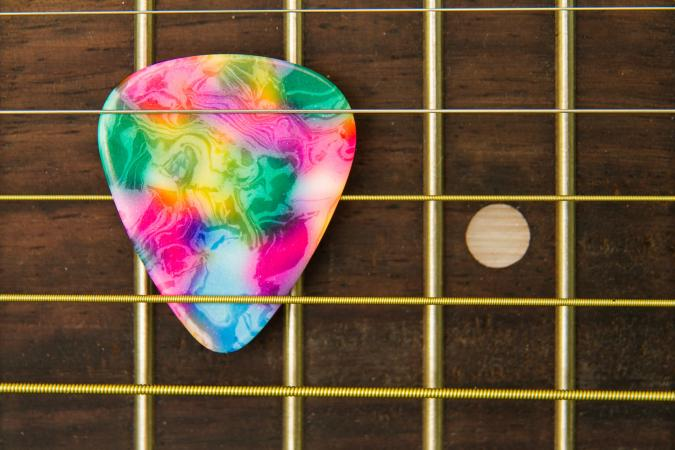 Close-Up Of Guitar With Colorful Pick