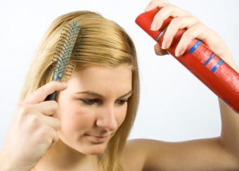 Woman using hair spray to style hair