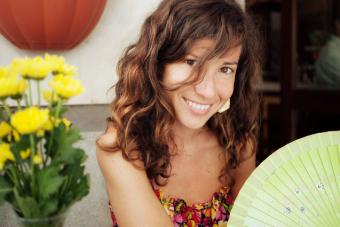 Woman with wavy hair holding fan