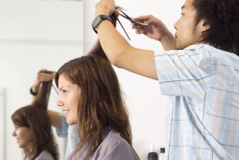 Hairdresser cutting woman's hair in salon