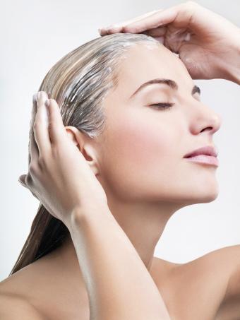 Young woman applying hair mask