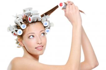Young woman using heated rollers