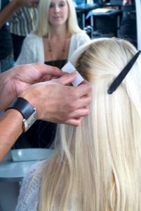 Woman getting blonde hair extensions