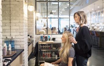Female hair stylist and customer talking