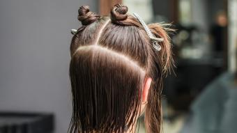 Dividing hair of woman in sections with clips