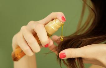 Woman applying oil on hair ends