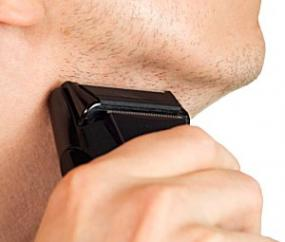 Man using an electic shaver under his chin