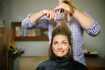 Nervous woman cutting long hair
