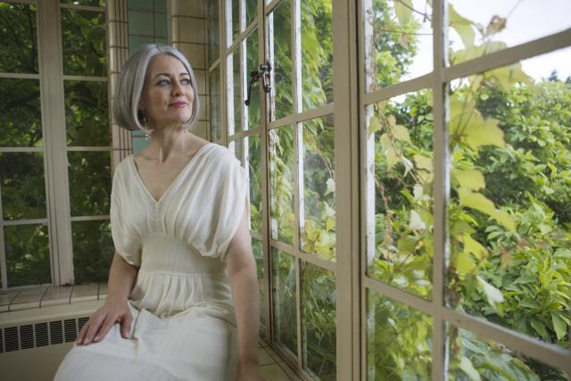 Mature woman sitting by garden window
