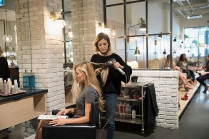 hairstylist with customer in hair salon