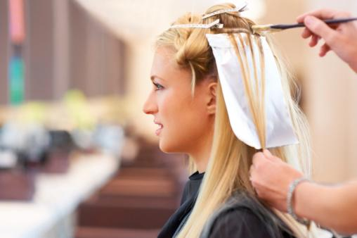 woman having her hair highlighted