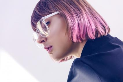 Stylish girl with pink hair and glasses