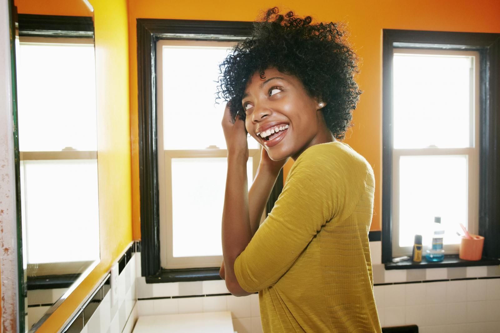 African American woman styling hair in bathroom mirror