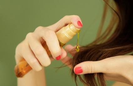 Woman applying oil on hair ends